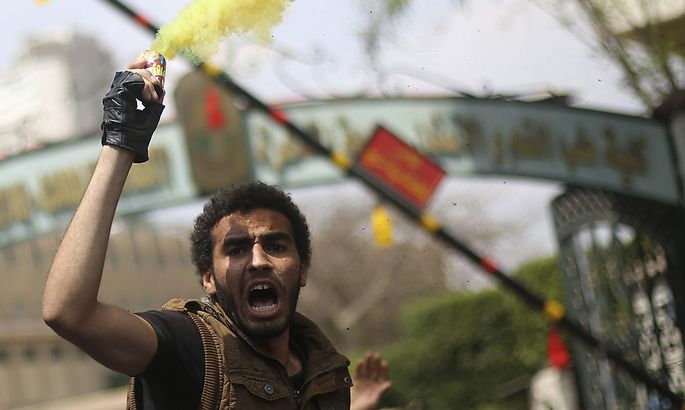 A student shouts slogans in protest against the military and interior ministry in front of the faculty of Oral & Dental Medicine in Cairo University