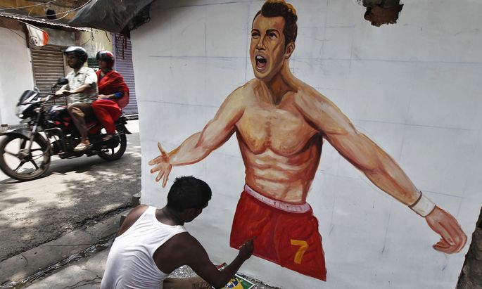 An artisan paints the wall of a house with a picture of Portugal´s national soccer player Cristiano Ronaldo, in Kolkata