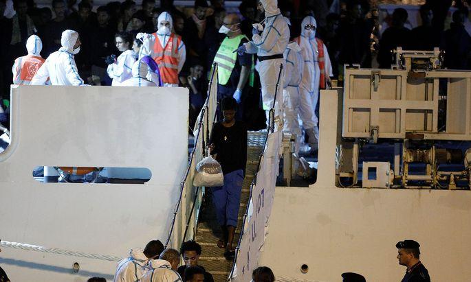 Unaccompanied minor migrants disembark from the Italian coast guard vessel 'Diciotti' at the port of Catania