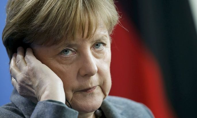 German Chancellor Merkel adjusts her earphones during news conference at the Chancellery in Berlin