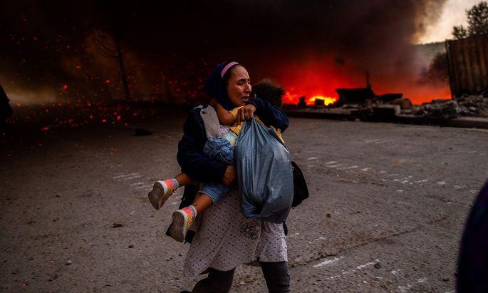 Eine Frau flieht mit einem Kind am 9. September vor dem Feuer im Flüchtlingslager Moria auf der Insel Lesbos.