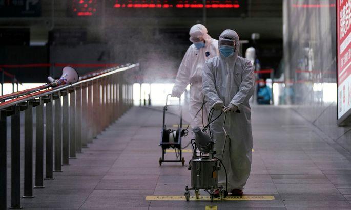 Arbeiter mit Desinfektionsgeräten in einem Bahnhof in Shanghai.