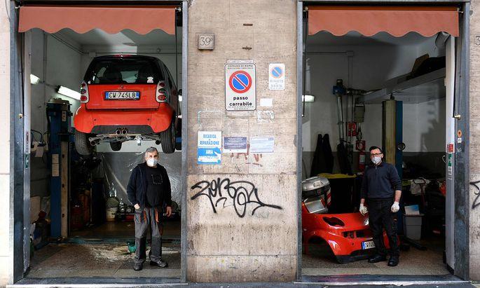 Mit Italien liegt Österreichs drittstärkster Handelspartner in wirtschaftlicher Agonie. Im Bild zwei Mechaniker am Donnerstag in ihrer Werkstatt in Rom.