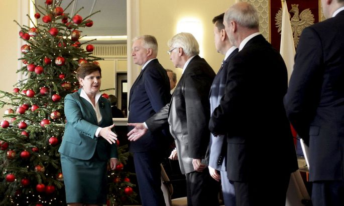 Polish Prime Minister Szydlo shakes hands with Foreign Minister Waszczykowski as she meets with other members of the cabinet in Warsaw