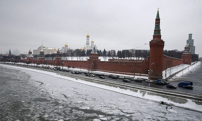 Vehicles travel along the embankment of the Moskva river past the Kremlin in the capital Moscow