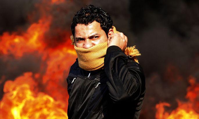 """""""Von allen Regimen seit 1952 führt as-Sisi das grausamste"""", sagt al-Aswani. Im Bild ein Demonstrant im Jänner 2011 in Kairo, vor brennender Barrikade."""