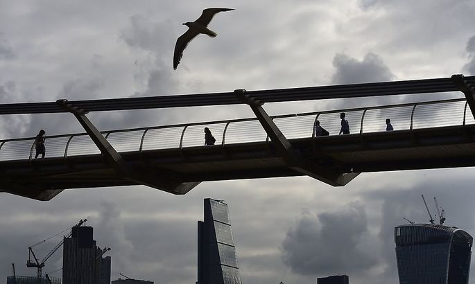 Workers cross the Millenium Bridge with the City of London seen behind, in London