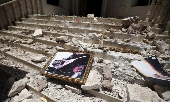 A picture of Saudia Arabia´s King Salman bin Abdulaziz lies amidst debris at damaged entrance to headquarters of Saudi Cultural Center in Sanaa, caused by April 20 air strike that hit nearby army weapons depot, in Sanaa