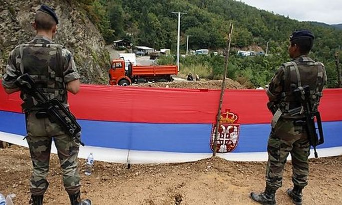 Serbian flag is seen as KFOR soldiers from France stand guard at the closed Serbia-Kosovo border cros