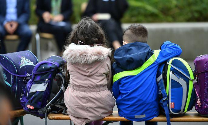 Erster Schultag in Nordrhein-Westfalen Zwei Schulkinder sitzen mit ihren Tornistern auf einer Bank vor der Schule. In No