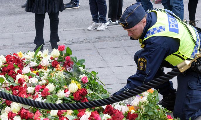 Ein Polizist legt Blumen in der Nähe des Tatortes in Zentral-Stockholm nieder.