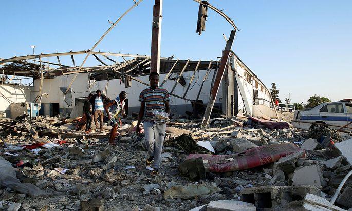 Überlebende suchen nach Verwertbarem in den Ruinen der Lagergebäude.