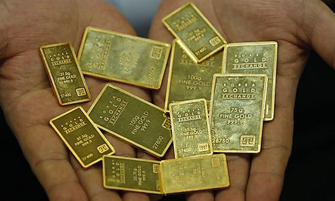 An employee at the Korea Gold Exchange shows off gold bars in Seoul, South Korea, Tuesday, Aug. 9, 20