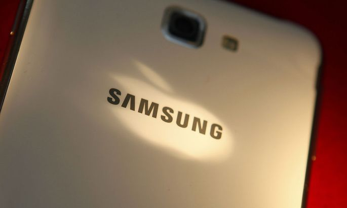 The logo of Apple Inc is reflected on the back of a Samsung Galaxy Note smartphone in this photo illustration taken in Beijing