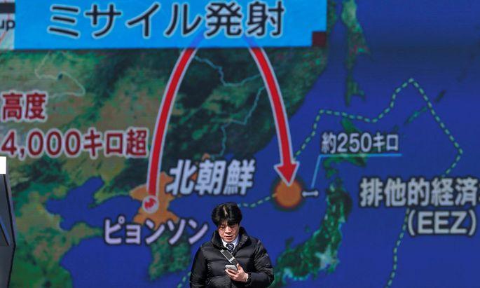 Ein Mann in Tokio vor einem Nachrichten-Monitor.
