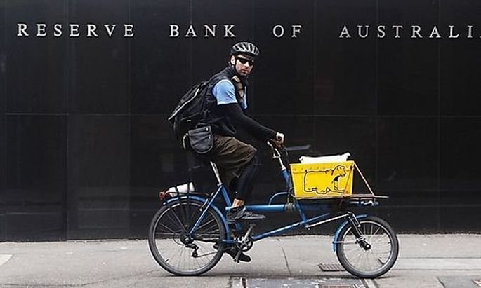 A worker rides past the Reserve Bank of Australia building in central Sydney