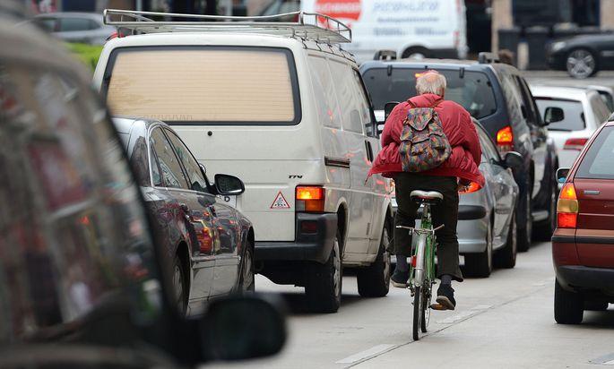 Ein Radfahrer im dichten Verkehr Wiens.