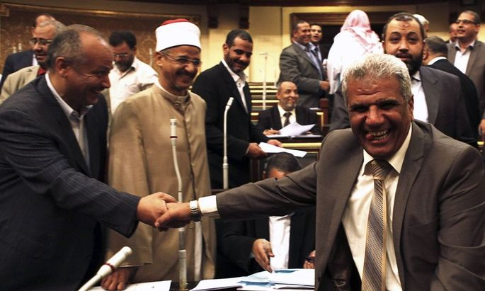 Islamist and Brotherhood members of the Shura Council, smile after the approval of the new judicial law during its meeting in Cairo