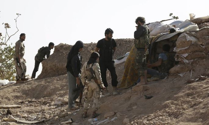 Free Syrian Army fighters of the 101 Division stand behind sandbags near the town of Morek in the northern countryside of Hama, Syria