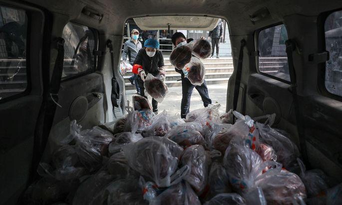 Lebensmittelverteilung im Corona-Epizentrum Wuhan: Die neue Krankheit befällt immer stärker auch die Weltwirtschaft.