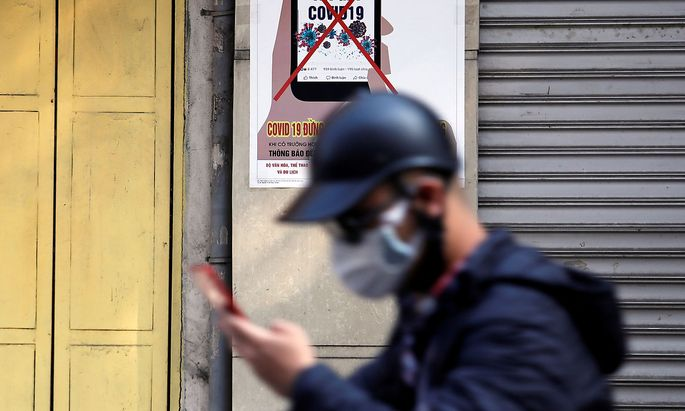 A man uses a smartphone as he walks past a poster warning against spreading 'fake news' on the coronavirus in Hanoi