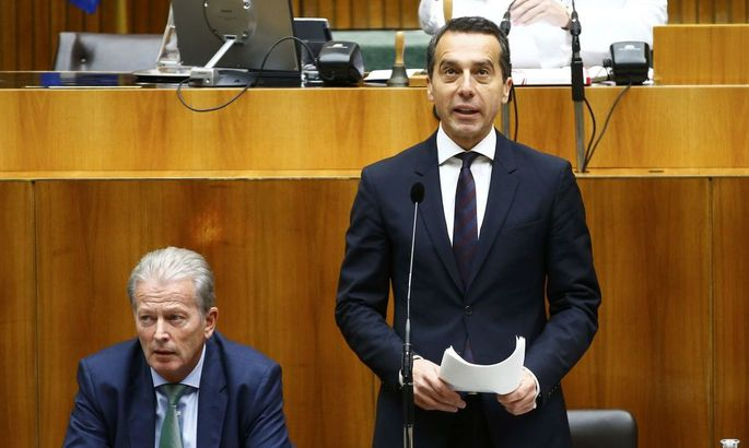 Austria's Chancellor Kern stands next to Vice Chancellor Reinhold Mitterlehner as he delivers a speech in the parliament in Vienna