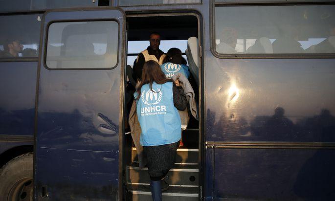 UNHCR-Mitarbeiter bringen Flüchtlinge in das Lager Moria auf Lesbos. Die Transfers will die Organisation nun einstellen.