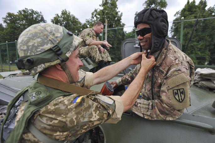 Ein Ukrainer zeigt einem Amerikaner, wie man eine Panzerhaube à la russe anlegt