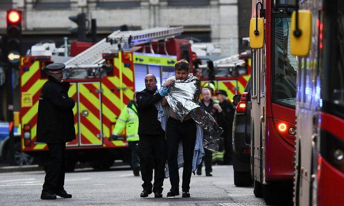 Einsatzkräfte bringen einen Verletzten in Sicherheit.