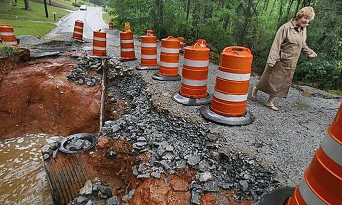 Susan Carman walks around a portion of roadway that washed away, Monday, May 3, 2010 in Douglasville,