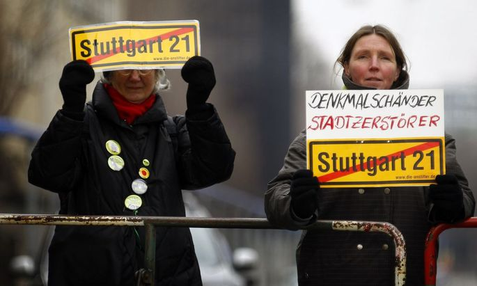 Demonstrators against the 'Stuttgart 21' train station project stand at a fence during the start of the demolition of a building of the main train station in Stuttgart