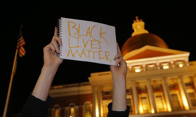 Man holds a sign reading ´Black Lives Matter´ in front of the State House in Boston