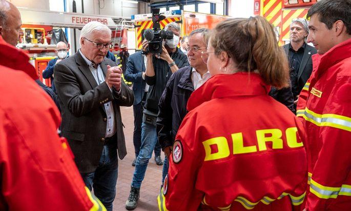 Bundespräsident Frank-Walter Steinmeier (links) und Armin Laschet (Mitte) beim Lokalaugenschein mit Helfern in Erftstadt.