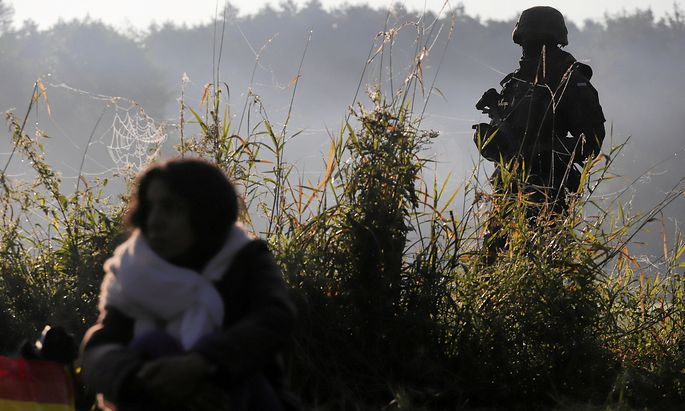 Polish servicemen and border patrol officers guard a group of migrants stranded on the border between Belarus and Poland near Usnarz Gorny