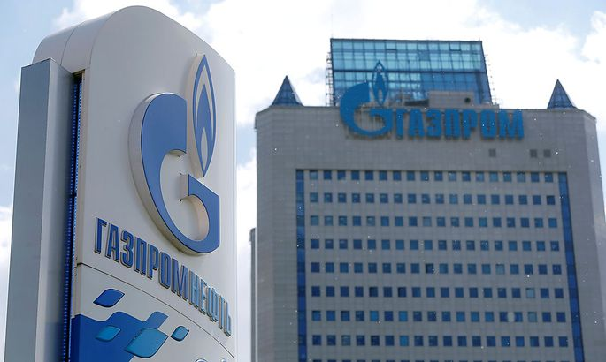 Board with Gazprom Neft oil company logo is seen at a fuel station in Moscow