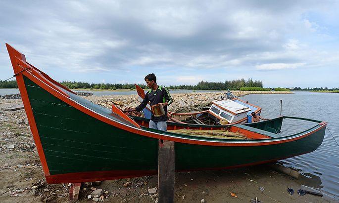 Ein Fischer restauriert sein Boot nach der Tsunami-Katastrophe von 2004. Mancherorts wurden zu viele neue Boote gespendet.