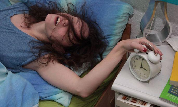 Junge Frau liegt im Bett und schlaeft Im Vordergrund ein Nostalgiewecker Junge Frau mit Wecker Zei