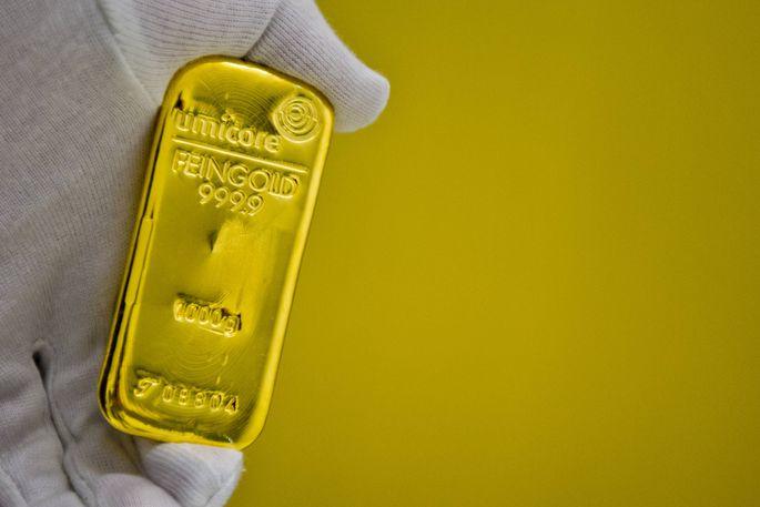 Eine Hand mit Handschuh haelt einen Goldbarren im Tresor des Goldhandels Pro Aurum Muenchen 16 02 2