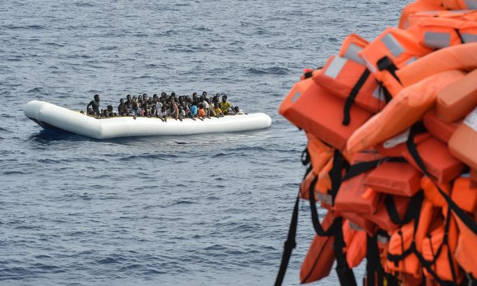 Symbolbild: Flüchtlinge in einem Schlauchboot blicken auf Rettungswesten
