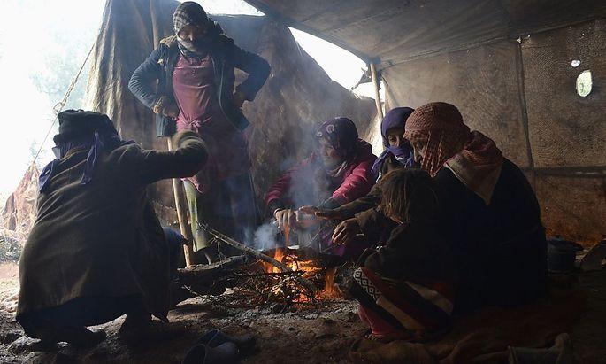 Syrische Flüchtlinge wärmen sich am Feuer.