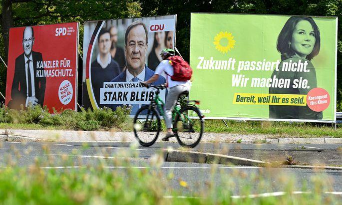 Radfahrerin fährt an Wahlplakaten mit den Spitzenkandidaten Olaf Scholz (SPD), Armin Laschet (CDU) und Annalena Baerbock (Bündnis 90/Die Grünen) vorbei.