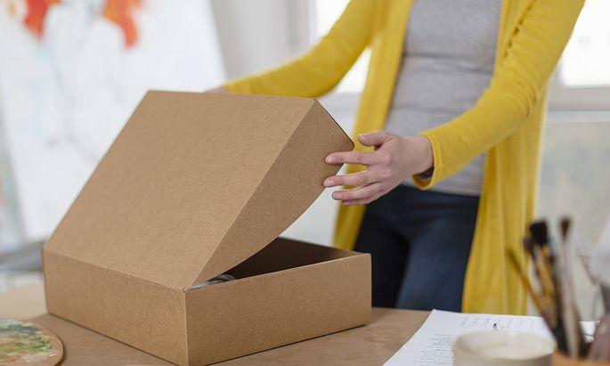 Woman unpacking cardboard box at home studio model released Symbolfoto property released EIF00552