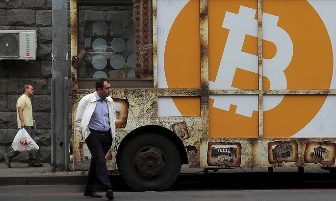 A board with the logo of Bitcoin is on display in Yerevan