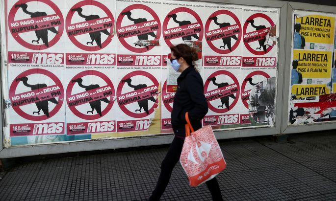FILE PHOTO: A pedestrian wearing a protective face mask walks past posters on the street that read 'No to the payment of the debt. Break with the IMF', in Buenos Aires