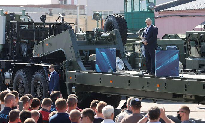 Präsident Lukaschenko beim Besuch im Minsker Radschlepperwerk (MZKT) am Montag. Vor den Toren der Fabrik schwangen Demonstranten die rot-weiße Fahne der Opposition.