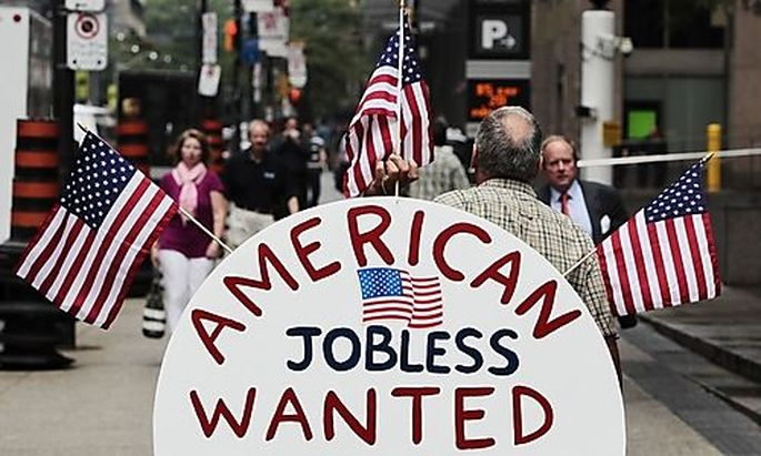 A man holds a sign reading American Jobless Wanted on the street ahead of the G20 summit in Toronto