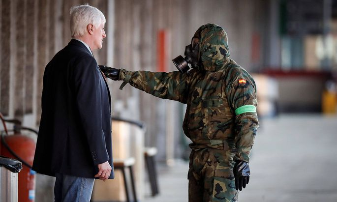 Ein spanischer Soldat stoppt einen Passanten, während seine Kameraden den Bahnhof der Stadt Irun desinfizieren.