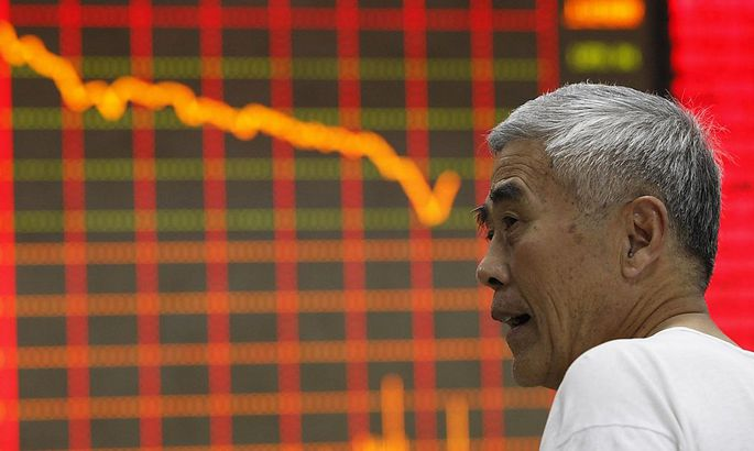 An investor stands in front of an electronic board showing stock information at a brokerage house in Huaibei