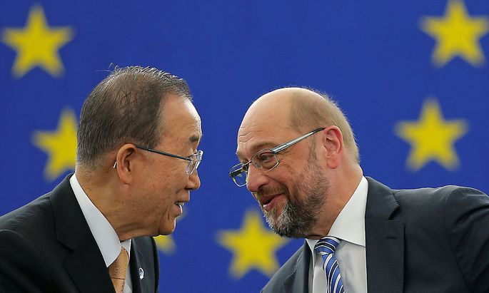 U.N. Secretary General Ban Ki-moon shakes hands with European Parliament President Schulz after the European Parliament vote in favor of the Paris UN COP21 Climate Change agreement in Strasbourg