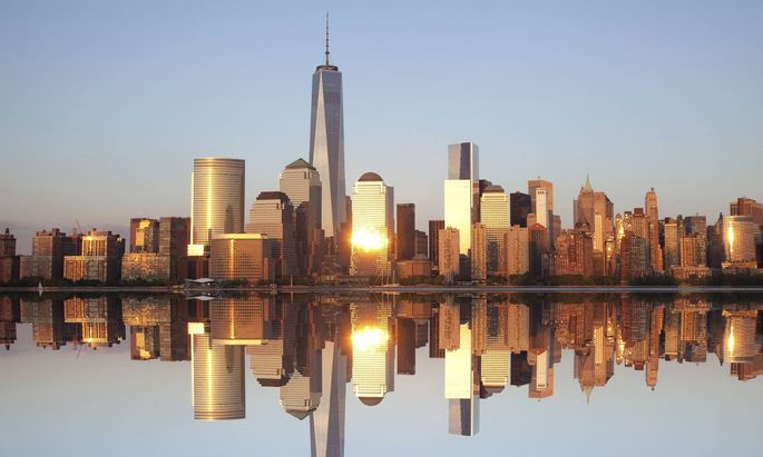 Skyline of Lower Manhattan reflected in calm Hudson River with skyscraper of One World Trade Center